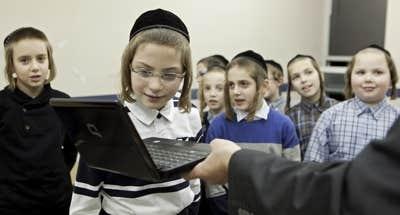 Un jeune garçon de l'école communautaire Belz (campus Durocher) lit ses répliques à l'ordinateur lors d'une pièce de théâtre.