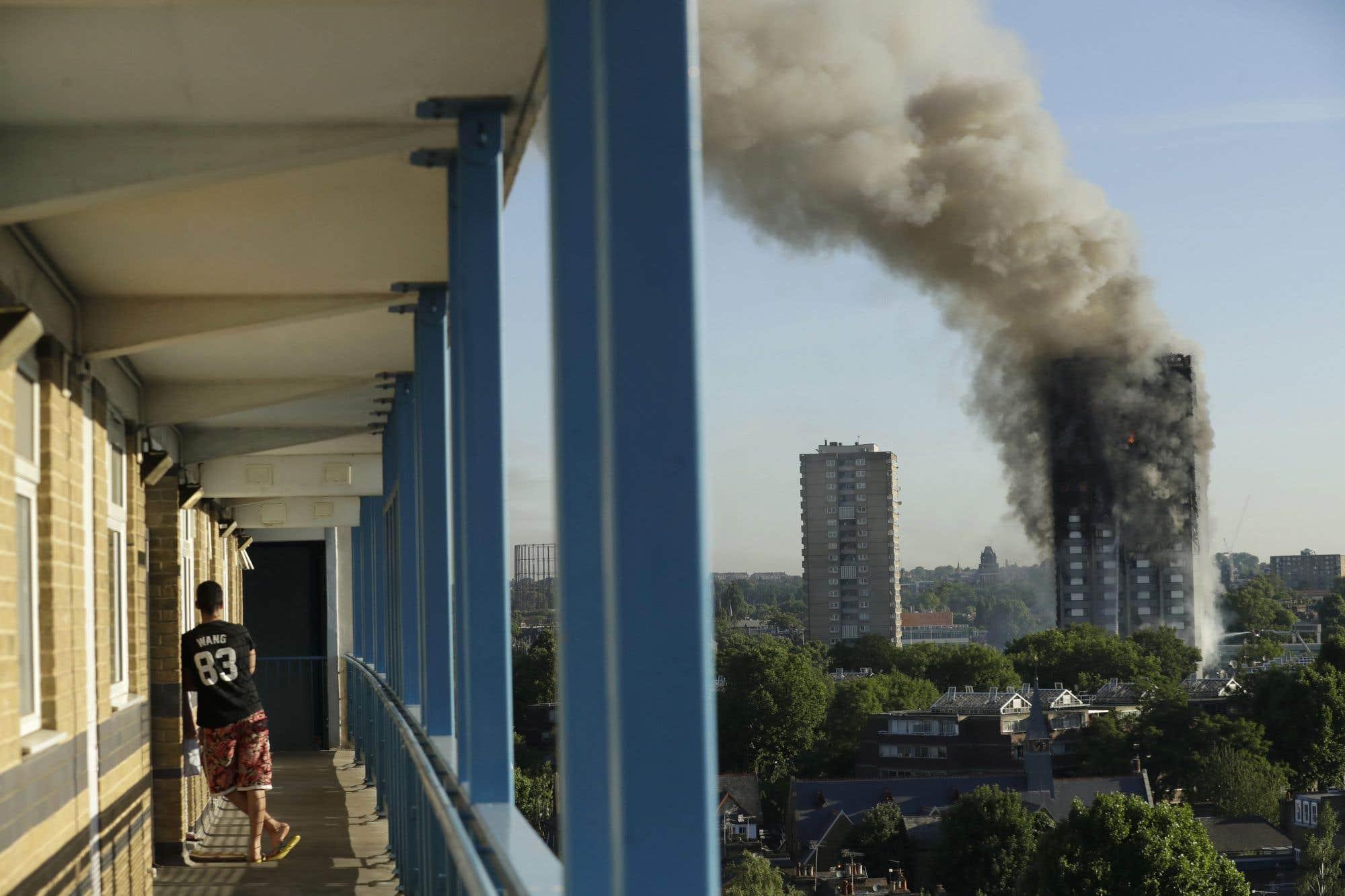 Un résident observe la fumée s'échapper de la tour Grenfell à Londres mercredi. L'édifice comprenait 120 logements et comptait 600 habitants. L'incendie qui s'est déclaré dans la nuit de mardi à mercredi s'était propagé en moins d'une heure à tout l'édifice et a pris 30 vies, selon le dernier bilan de la police britannique. La première ministre Theresa May a ordonné une enquête sur les causes de l'incendie jeudi.