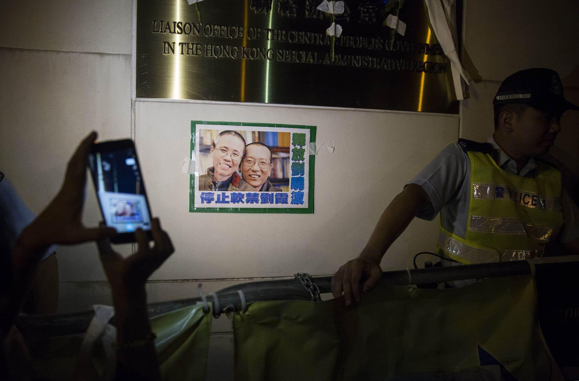 Une photo du lauréat du prix Nobel de la paix Liu Xiaobo est installée sur le mur du bureau de liaison avec la Chine de Hong Kong. Le dissident chinois, un symbole de la démocratie, est décédé d'un cancer du foie à l'hôpital de Shenyang. Il est devenu le premier lauréat d'un prix Nobel à mourir en détention depuis 1938. Consultez notre texte sur le sujet