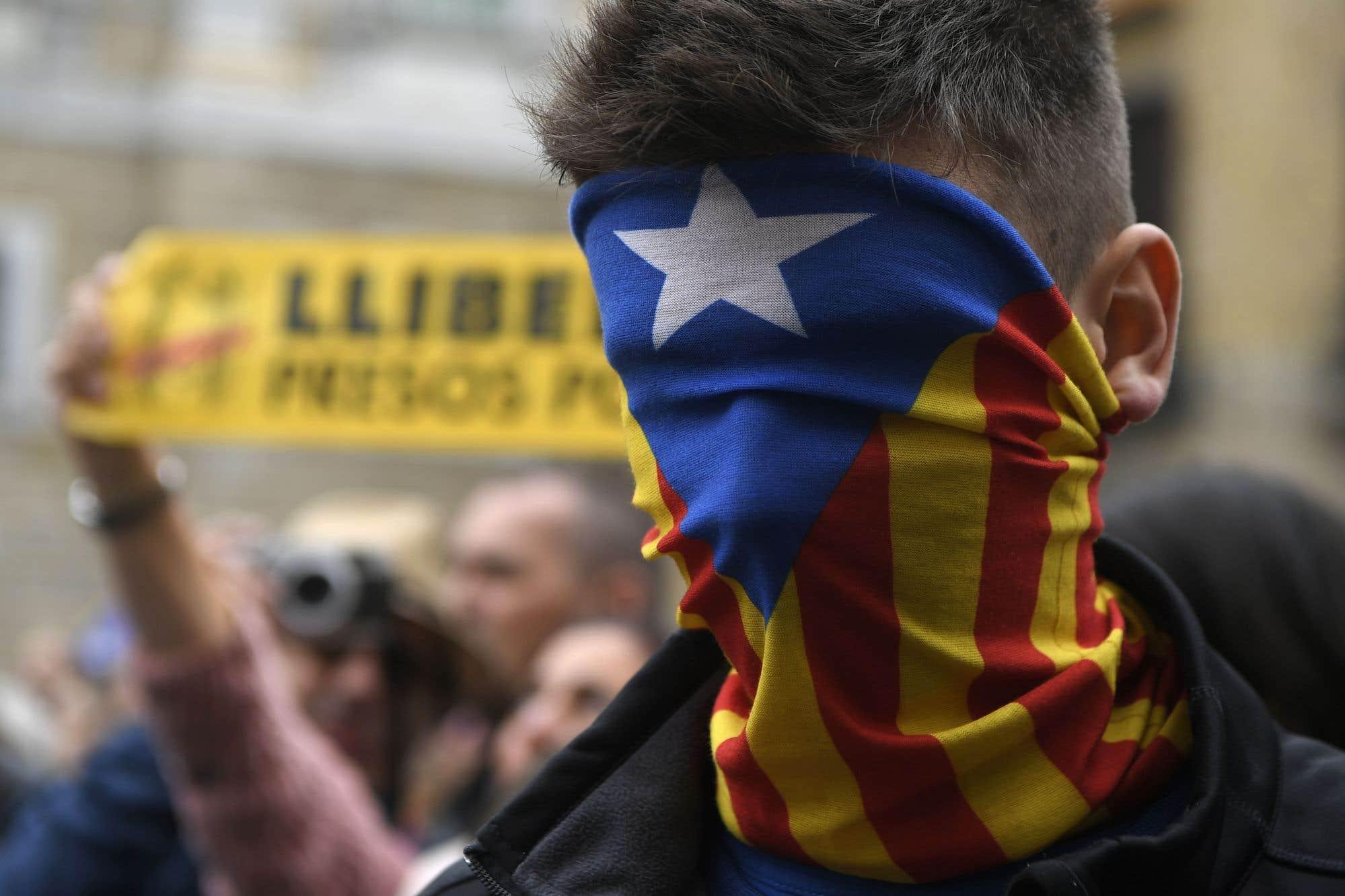 Un homme portant le drapeau catalan en guise de masque assiste à une manifestation devant le Palais de la Generalitat à Barcelone. Les manifestants ont bloqué des routes, des autoroutes et des voies ferrées dans le cadre d'une grève régionale organisée par des indépendantistes.