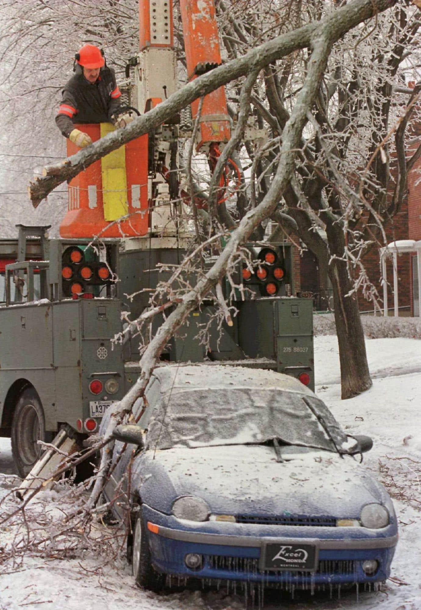 Un employé de la Ville de Montréal coupe les branches d'un arbre qui a endommagé un véhicule. Au total, le coût des dommages dans toutes les régions du Canada touchées par la tempête de verglas a été évalué à 5,4 milliards de dollars.
