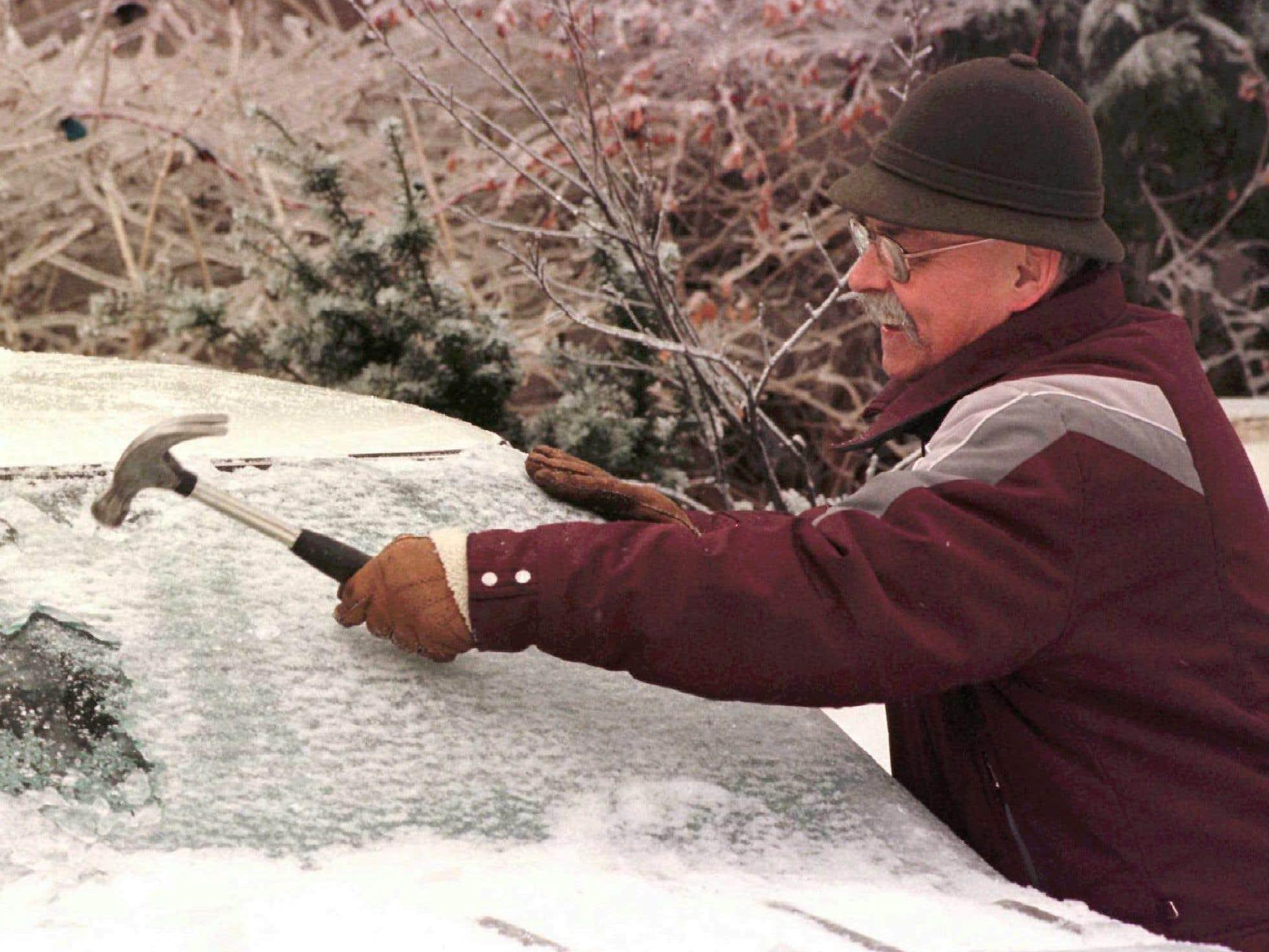 Un Montréalais utilise un marteau pour enlever la glace accumulée sur le pare-brise de son véhicule. À ce moment, des précipitations de pluie verglaçante étaient à prévoir pour encore deux jours.