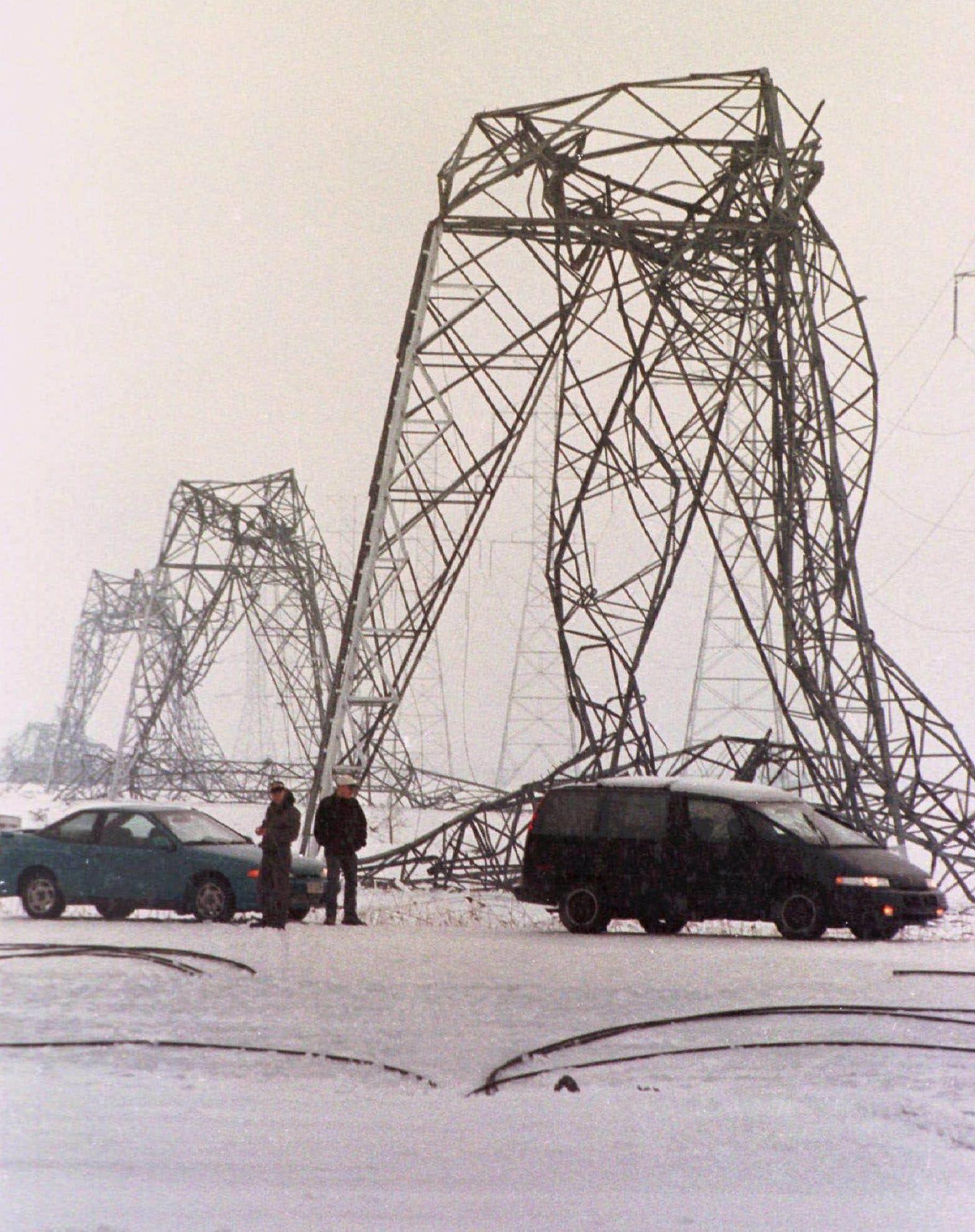 Des automobilistes observent des pylônes endommagés près de Saint-Bruno-de-Montarville, en Montérégie. Au cours de la crise du verglas, plus de 3000 structures du réseau de transport d'Hydro-Québec se sont effondrées, dont un millier de pylônes en acier.