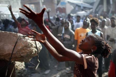 Une jeune fille tend les bras vers des pillards afin de recevoir quelques biens dérobés dans un magasin éventré de Port-au-Prince, hier.