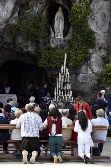 Des pèlerins se recueillent devant la Vierge, à Lourdes.