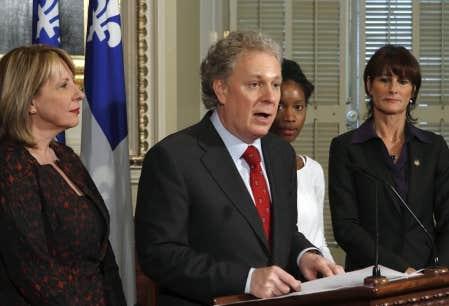 Christine St-Pierre, Yolande James et Kathleen Weil entouraient le premier ministre Jean Charest hier, lors de la présentation du projet de loi.
