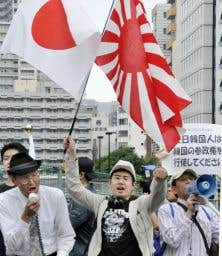 Des militants de droite japonais brandissent des drapeaux nationaux à Tokyo, en 2009, alors que quelque 700 étrangers, principalement des résidents sud-coréens, organisent un rassemblement pour exiger le droit de vote aux élections locales.