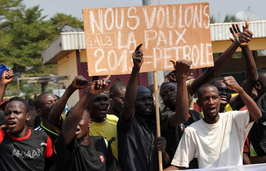 Des manifestants brandissaient des pancartes en criant des slogans à l'intention du président centrafricain François Bozizé, qui débarquait à l'aéroport de Bangui accompagné du président de l'Union africaine, ce dimanche.