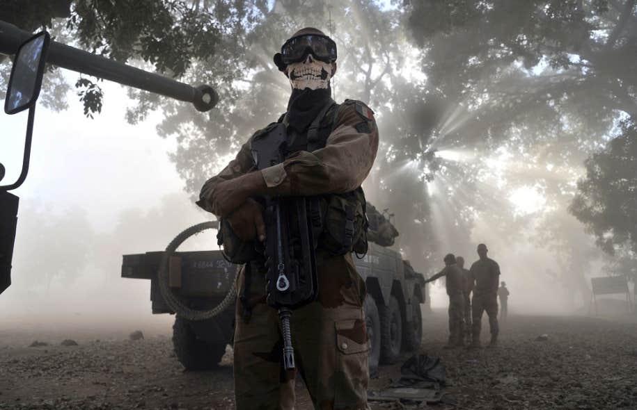 Un soldat français portant un foulard se tient près d'un char d'assaut dans une rue de la ville de Niono, où les forces régulières françaises au Mali se sont déployées dimanche.
