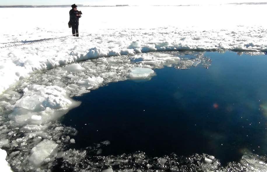 Cette photo fournie par la police de la région de Tcheliabinsk, en Russie, montre un trou de six mètres de diamètre qu'aurait créé, au milieu d'un lac gelé, la météorite tombée vendredi.