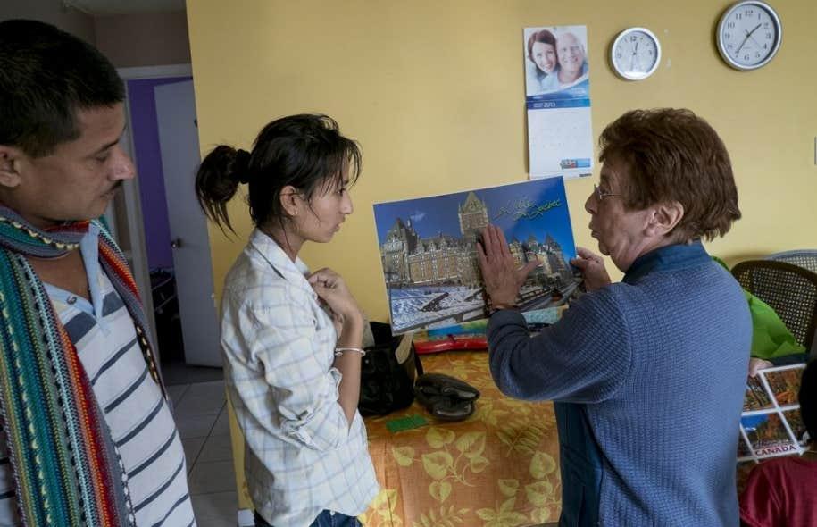 En visite chez la famille Khatiwada, la bénévole Denise Blouin montre à une jeune fille le Château Frontenac sur un calendrier.Mme Blouin veille au sort des réfugiés népalais de son quartier de Québec.