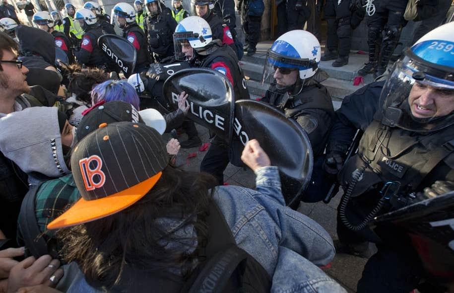 Les policiers repoussant des manifestants aux portes de l'hôtel de ville de Montréal lundi soir. La journée a donné lieu à plusieurs manifestations dénonçant le règlement P-6, qui limite le droit de manifester.