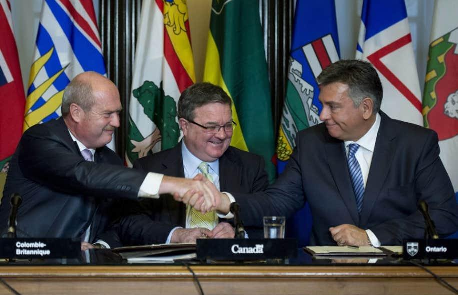 Le ministre des Finances du Canada, Jim Flaherty, regarde ses homologues de la Colombie-Britannique et de l'Ontario, Mike de Jong et Charles Sousa, échanger une poignée de mains lors de la conférence de presse portant sur le projet de commission unique des valeurs mobilières.