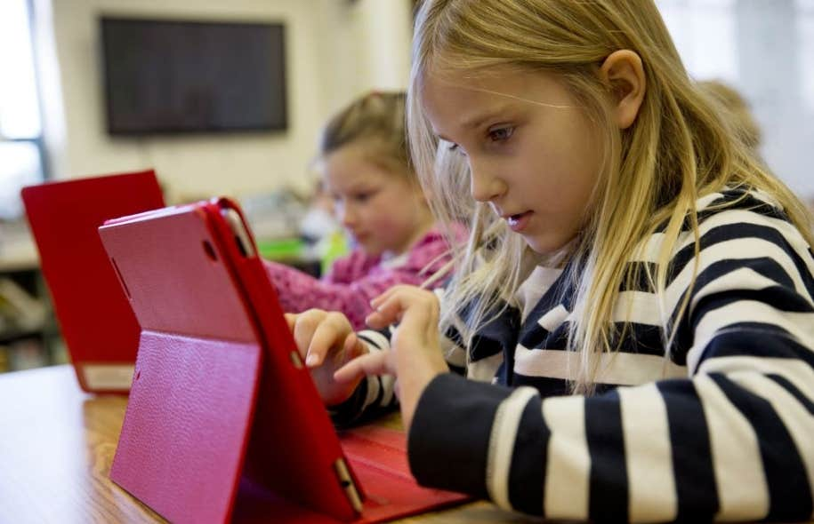 Utilisé dans les classes du Québec et des États-Unis (ci-haut, en Virginie), le iPad permet aux élèves de consulter les versions électroniques deleurs manuels scolaires.