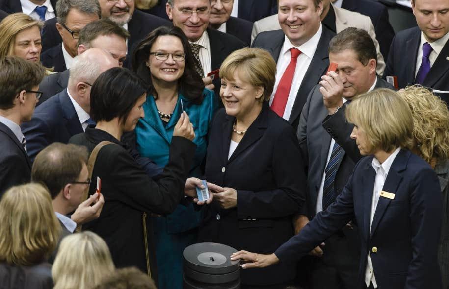 Angela Merkel était tout sourire en déposant son bulletin de vote, mais ce n'est pas sans quelques grincements de dents qu'elle et plusieurs de ses députés ont adopté la Loi sur le salaire minimum en Allemagne.