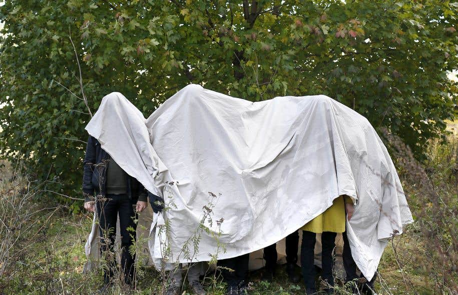 Des membres du collectif Entrepreneurs du Commun posent sous une couverture afin d'illustrer l'instrumentalisation du mémorial par le gouvernement Harper.