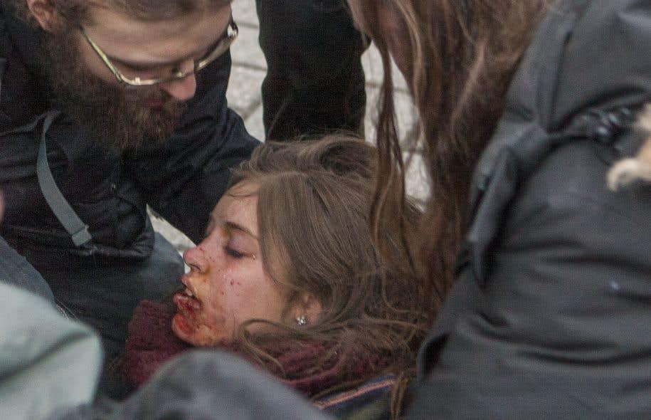 Naomie Tremblay-Trudeau a été atteinte au visage par le projectile d'un policier alors qu'elle participait jeudi à une manifestation. Des camarades tentent ici de lui porter secours immédiatement après l'événement.