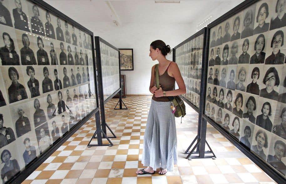 Le régime de Pol Pot a fait plus d'un million de victimes au Cambodge. Cette touriste scrute les photos de quelques-unes d'entre elles à Phnom Penh.
