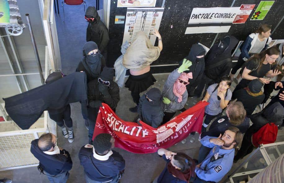 Des étudiants masqués manifestent à l'UQAM.