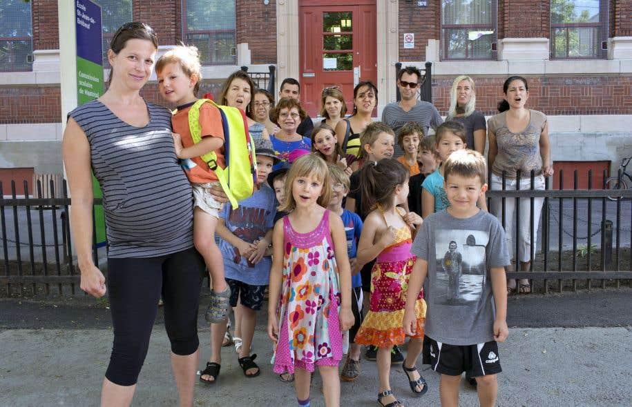 Des parents du regroupement Je protège mon école publique, devant l'école Saint-Jean-de-Brébeuf, à Montréal. À droite, la porte-parole Pascale Grignon.