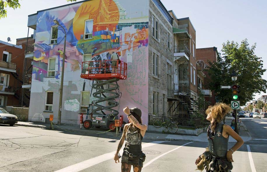 L'artiste montréalais Fluke poursuivait vendredi la réalisation d'une immense œuvre sur le mur latéral d'un bâtiment de la rue Sainte-Catherine Est, à l'angle de la rue Joliette.