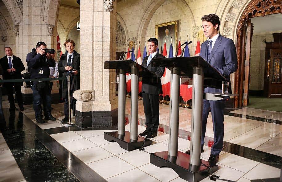 Pour le cliché mettant en vedette le premier ministre et son homologue français, Manuel Valls, lors d'une conférence de presse, l'artiste s'est métamorphosé en journaliste, calepin à la main, pour se fondre dans le décor diplomatique du parlement.