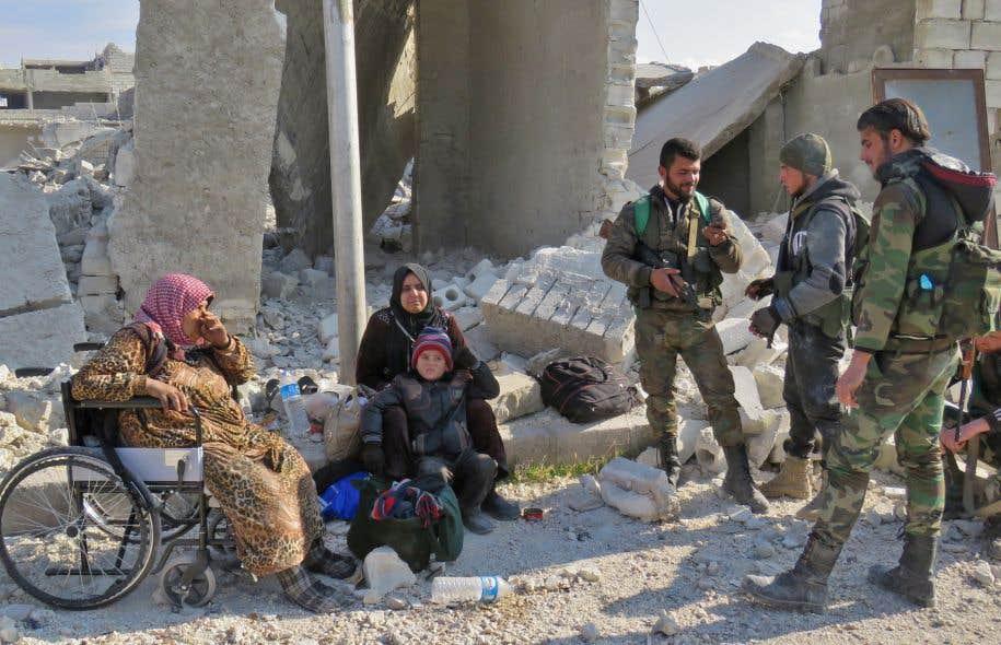 Des soldats du régime syrien discutent avec des résidents d'Alep, après avoir repris possession de cette zone aux dépens des forces rebelles.