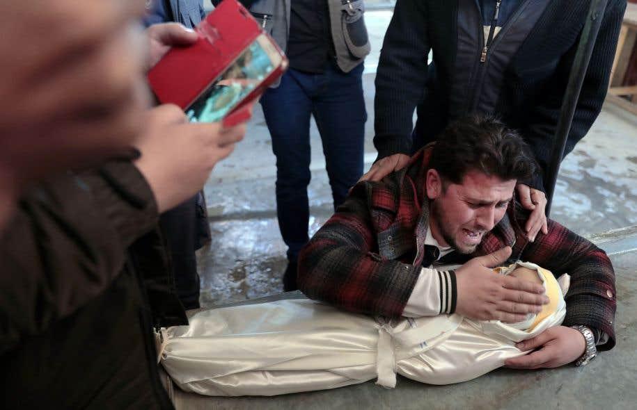 Un père pleure la mort de son bébé d'un an, victime d'un bombardement des forces d'Al-Assad à Douma, une ville tenue par les rebelles.