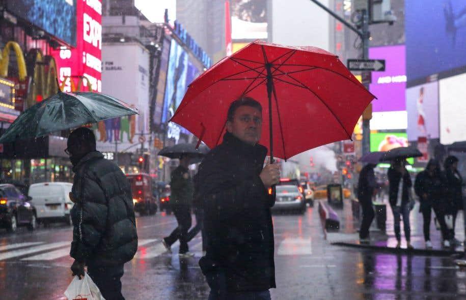 Des gens se promènent sous la pluie à Times Square le 5 mai 2017 alors que des avertissements d'inondations sont en vigueur pour la région de New York.