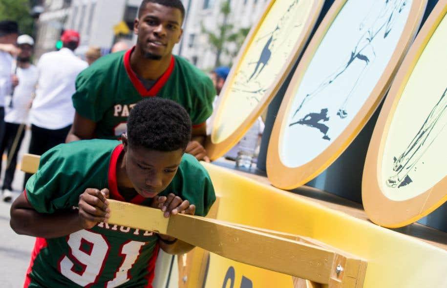 De jeunes hommes noirs ont poussé des chars allégoriques lors du défilé de la Saint-Jean, samedi à Montréal.