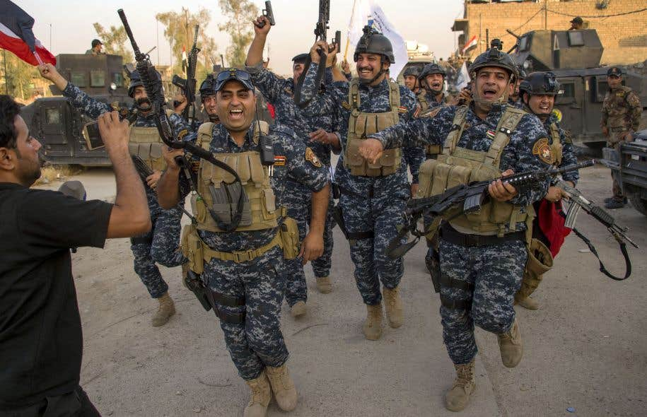 Des dizaines de membres des forces de sécurité ont explosé de joie dans les rues de Mossoul en chantant en dansant et en brandissant les drapeaux irakiens ou leurs armes en signe de victoire