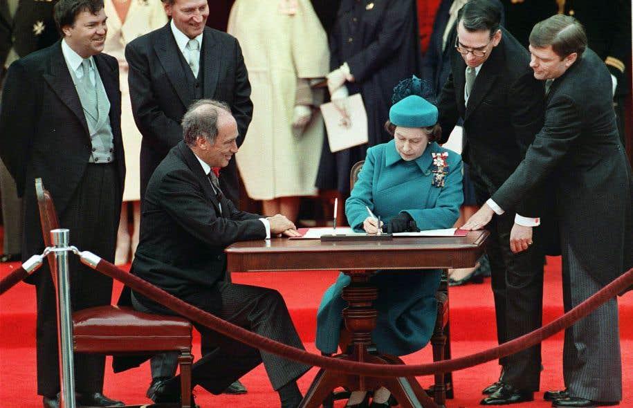 Signature de la Constitution canadienne par la reine Elizabeth II, en présence du premier ministre Pierre Elliott Trudeau, en avril 1982. L'analyse par Dalie Giroux de l'aberrante continuité occulte entre l'ancien colonialisme de Londres et le nationalisme actuel d'un Parti québécois dégénéré est troublante.