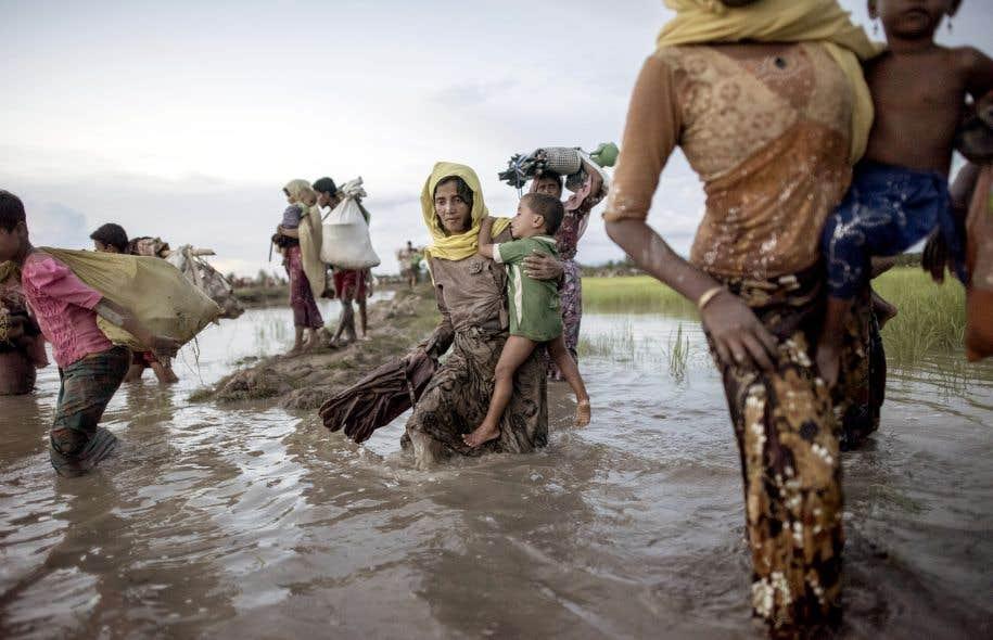 Des réfugiés rohingyas traversaient lundi la rivière Naf, qui relie le Myanmar au Bangladesh. Ils sont environ 2000 à s'exiler chaque jour, selon l'Organisation internationale pour les migrations.