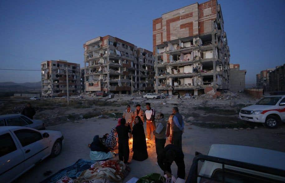 Devant des bâtiments fragilisés par le tremblement de terre, des rescapés tentent de se réchauffer autour d'un feu pour combattre la fraîcheur de la nuit à Sar-e Pol-e Zahab, la ville la plus touchée par le sinistre, avec 280 morts.