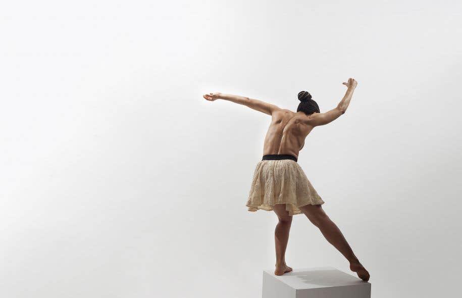 À demi-nue, un jupon autour des hanches, Sarah Elola apparaît avec un cube en bois en équilibre sur la tête avant qu'il ne se dirige vers le sol et devienne socle.