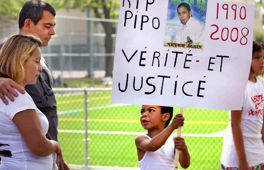 En hommage à Fredy Villanueva, un enfant brandit une pancarte lors d'une marche commémorative en 2011 à Montréal-Nord.