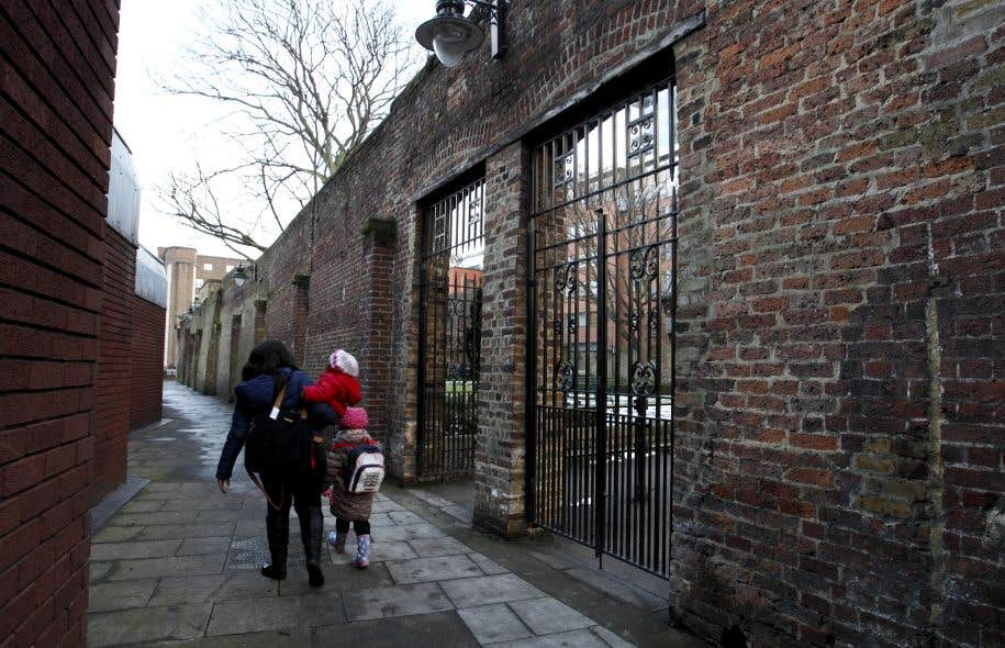 Une jeune femme et des enfants passent devant un des murs qui restent de la prison dans laquelle le père de Charles Dickens a été emprisonné plusieurs mois à cause de dettes.