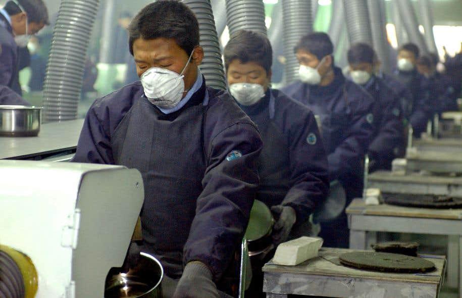 Des travailleurs nord-coréens besognent dur dans une usine de fabrication de poêles et de chaudrons installée dans le parc industriel de Kaesong, créé en 2002 à la suite d'un accord conjoint entre les Corées du Sud et du Nord, mais rompu en 2016.