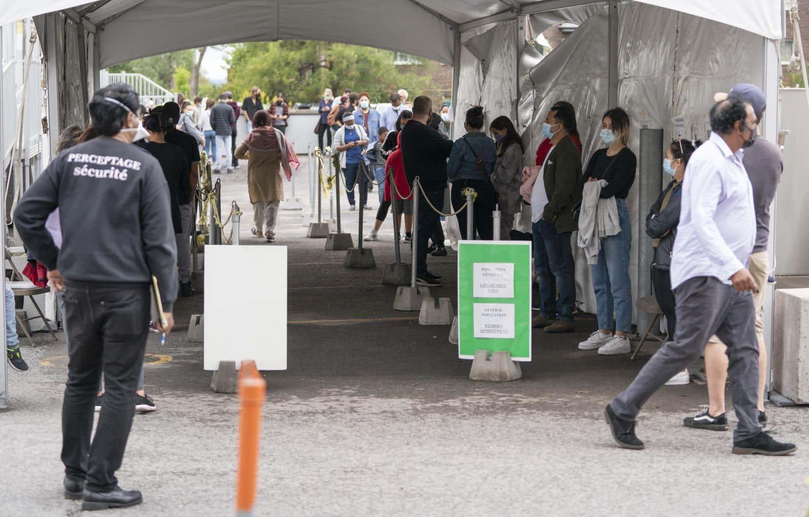 Des gens font la file à une clinique de dépistage de la COVID-19 à Montréal.