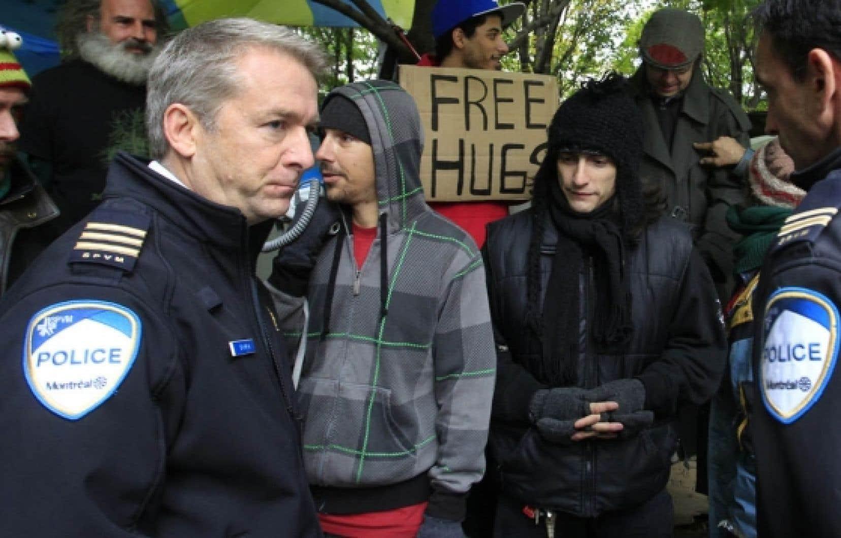 Des policiers de Montr&eacute;al et des indign&eacute;s discutent des meilleures fa&ccedil;ons d&rsquo;assurer une occupation pacifique du square Victoria. <br />