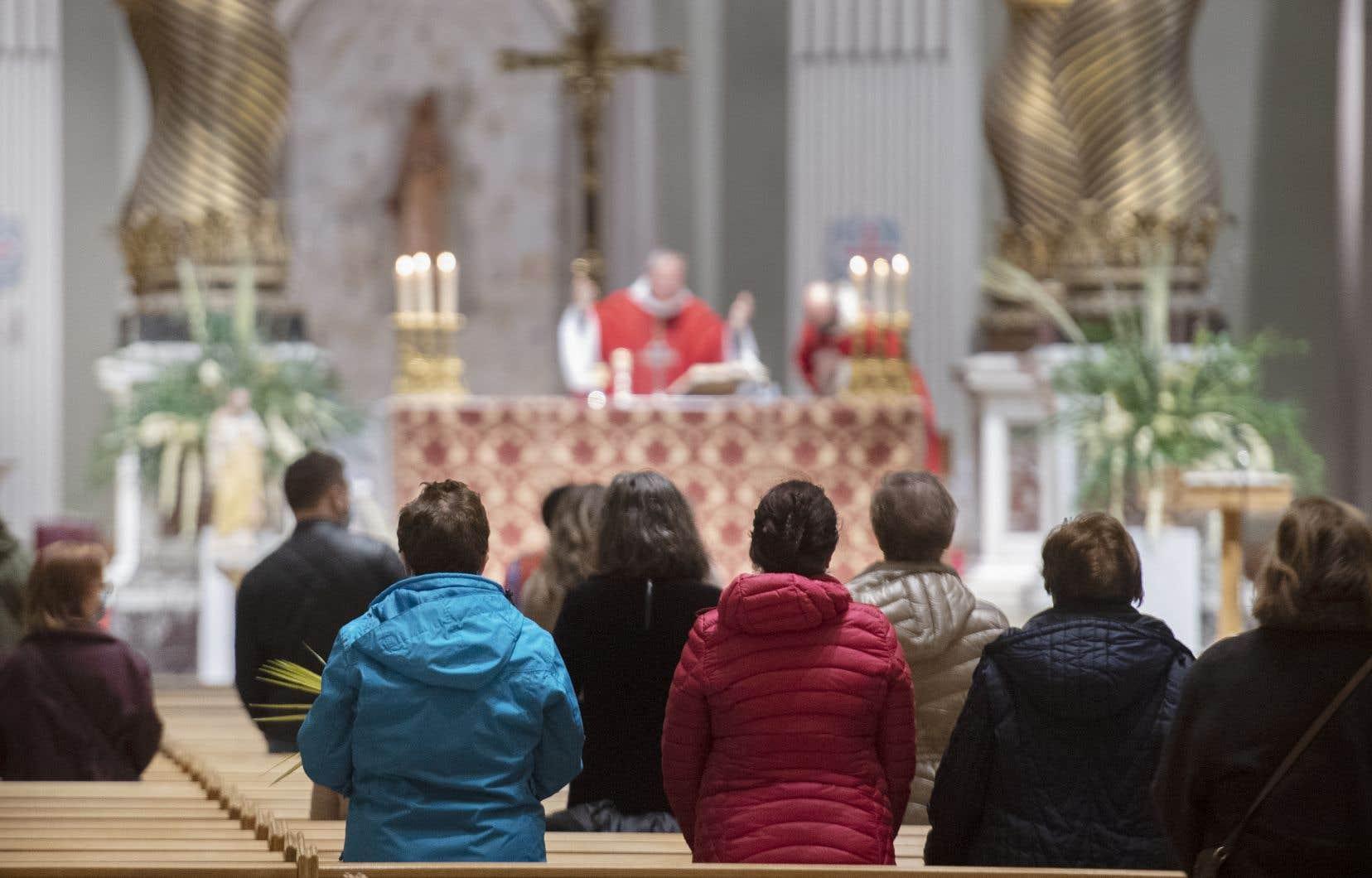 Des fidèles assistent à une messe à la cathédrale Marie-Reine-du-Monde à Montréal, le dimanche 28 mars 2021.