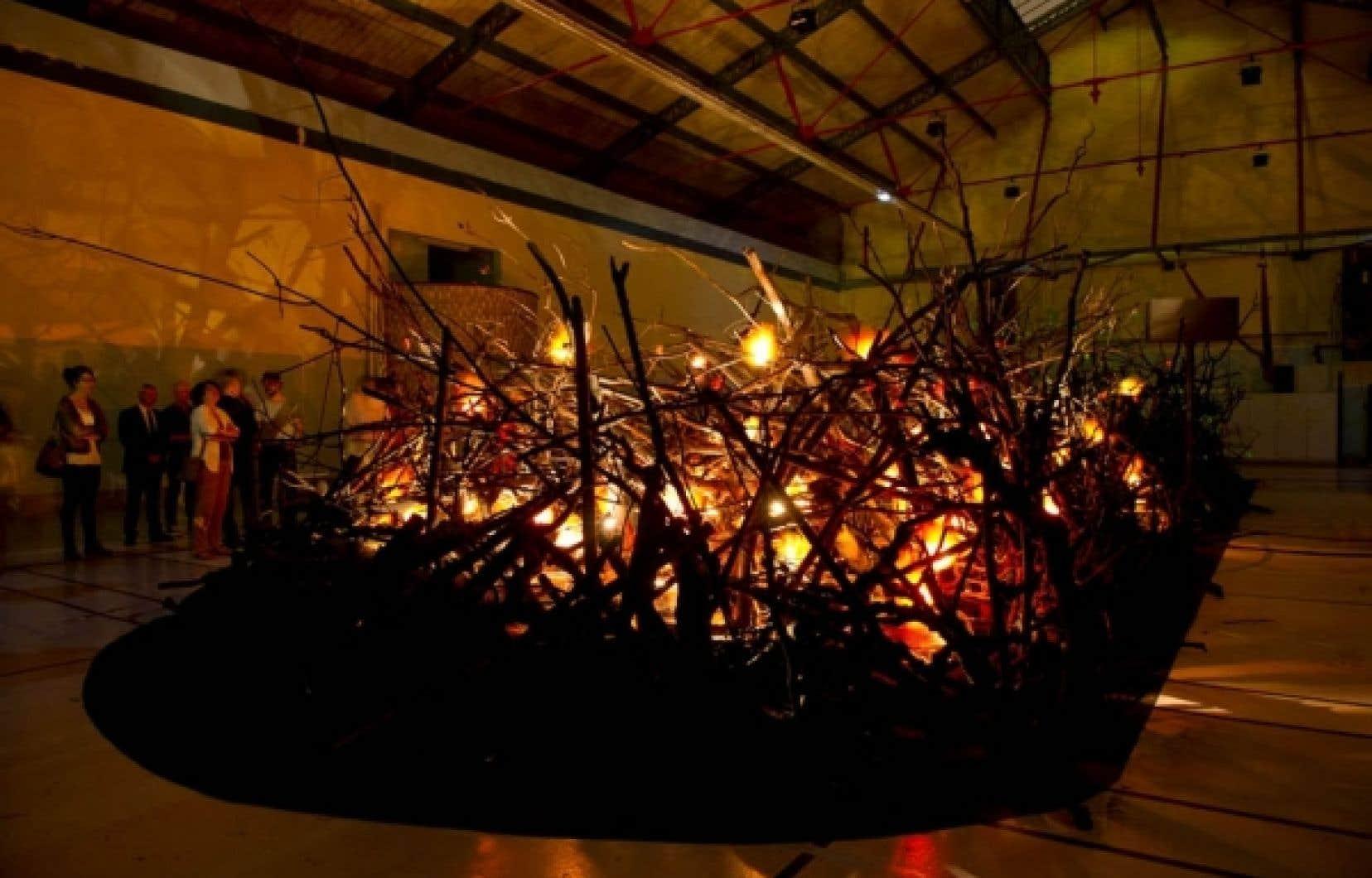 L'installation Spectacles + Problèmes simule un bûcher avec des flammes factices faites de rubans colorés. <br />