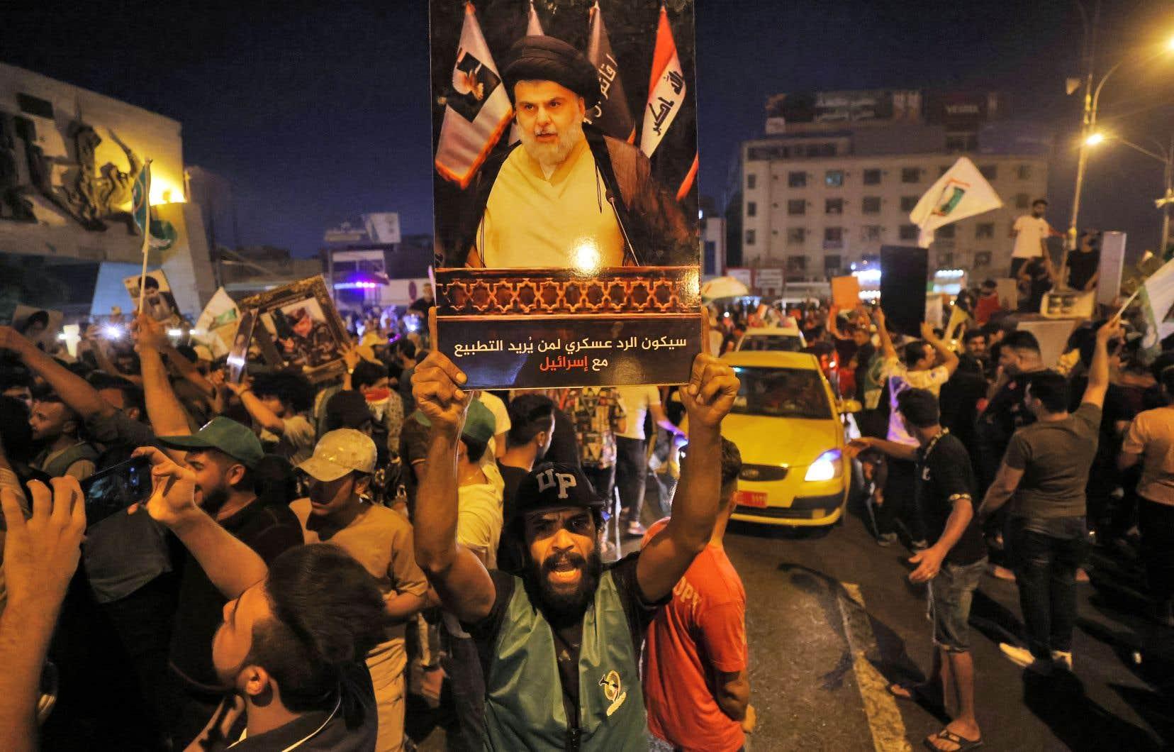 Sur la place Tahrir dans le centre de Bagdad, où se mêlaient klaxons, youyous et pétards de célébration, quelques centaines de sadristes se sont rassemblés, brandissant drapeaux irakiens, fanions du mouvement et portraits de leur leader, Moqtada al-Sadr.
