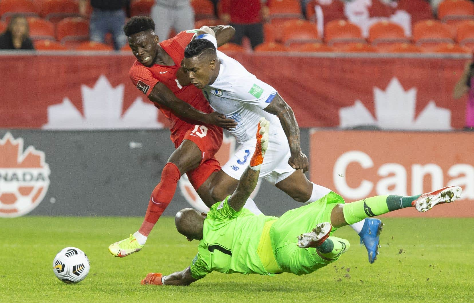 Le Canadien Alphonso Davies (à gauche) contourne le gardien du Panama Luis Mejia sous le regard d'Harold Cummings lors de la première mi-temps des qualifications pour la Coupe du monde à Toronto.