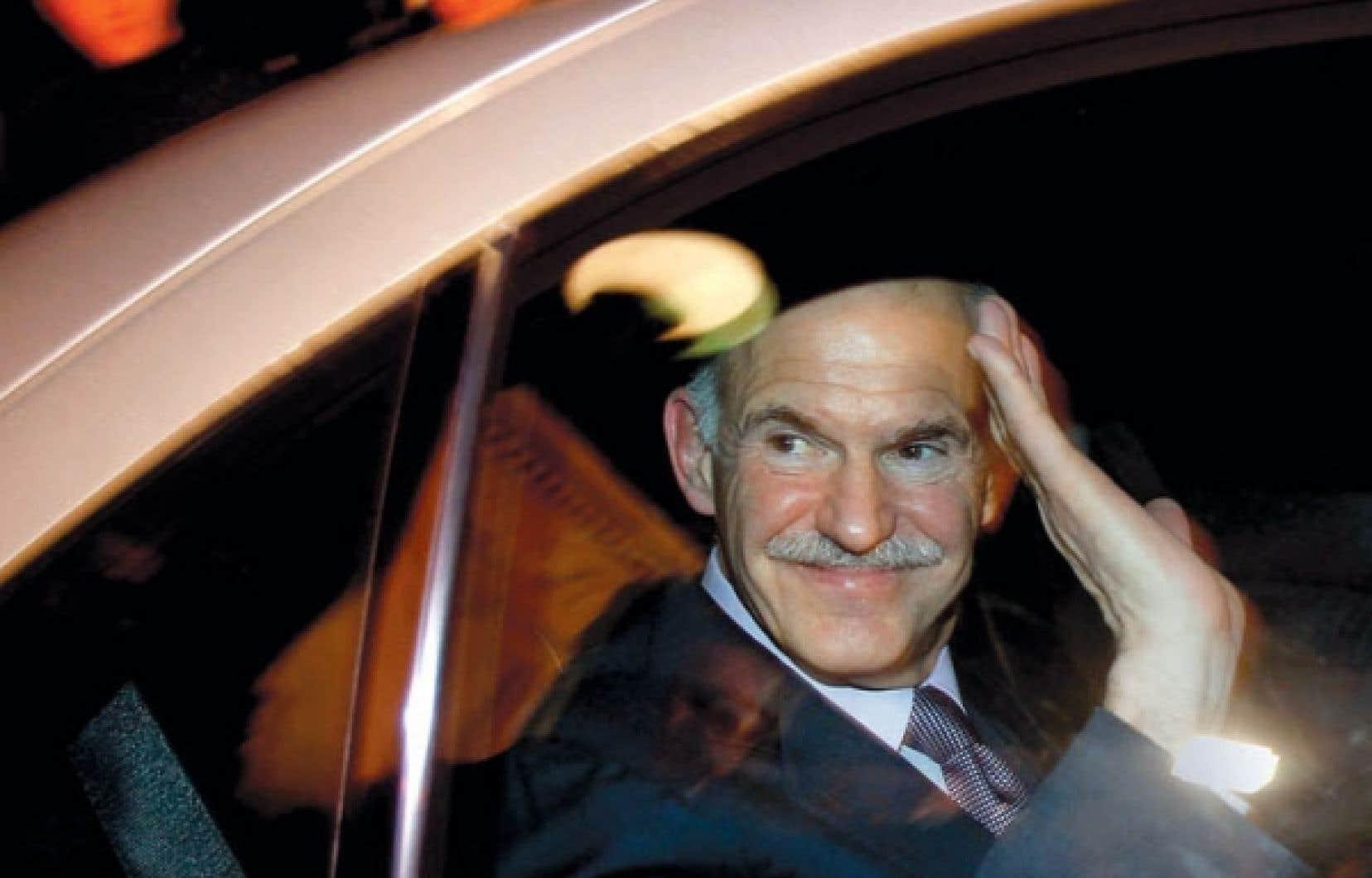 Le premier ministre grec, George Papandréou, faisant un signe de la main à bord de sa voiture en quittant le palais présidentiel, à Athènes, hier, après avoir négocié avec l'opposition la formation d'un gouvernement de coalition, qu'il ne dirigera pas et qui aura pour tâche de sortir le pays d'une grave crise. <br />