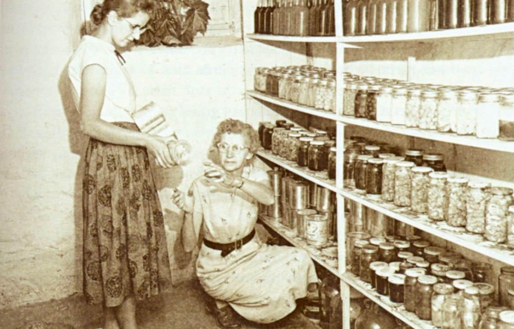 Un garde-manger rempli de pots de confiture variées. Mme Phiippe Pépin et sa fille Denise, Warwick, Arthabasca, 1957.