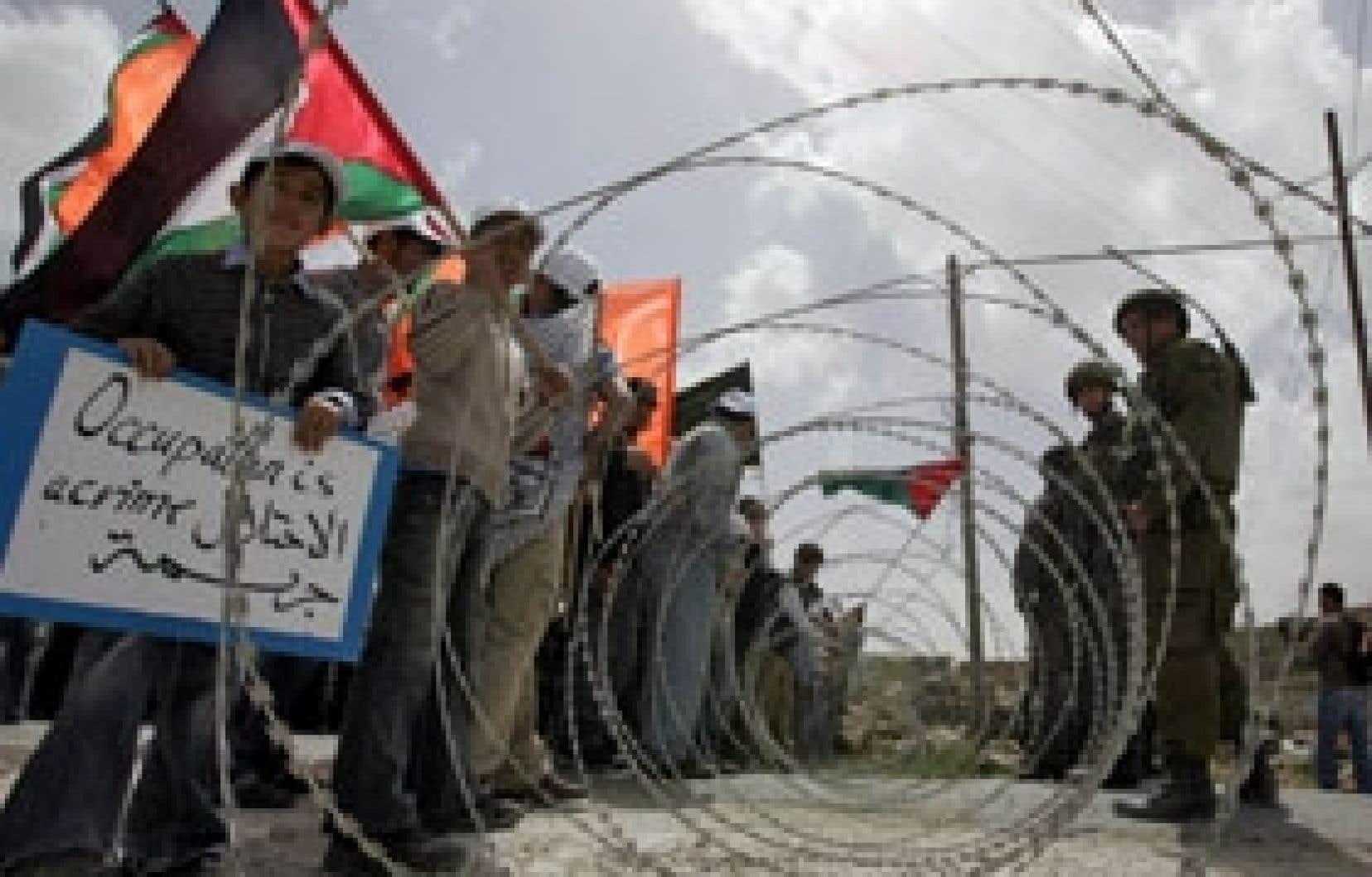 Drapeaux à la main, des Palestiniens font face à des soldats israéliens dans le village d'Umm Salamunah, en Cisjordanie, qui a été le théâtre d'une manifestation hier.