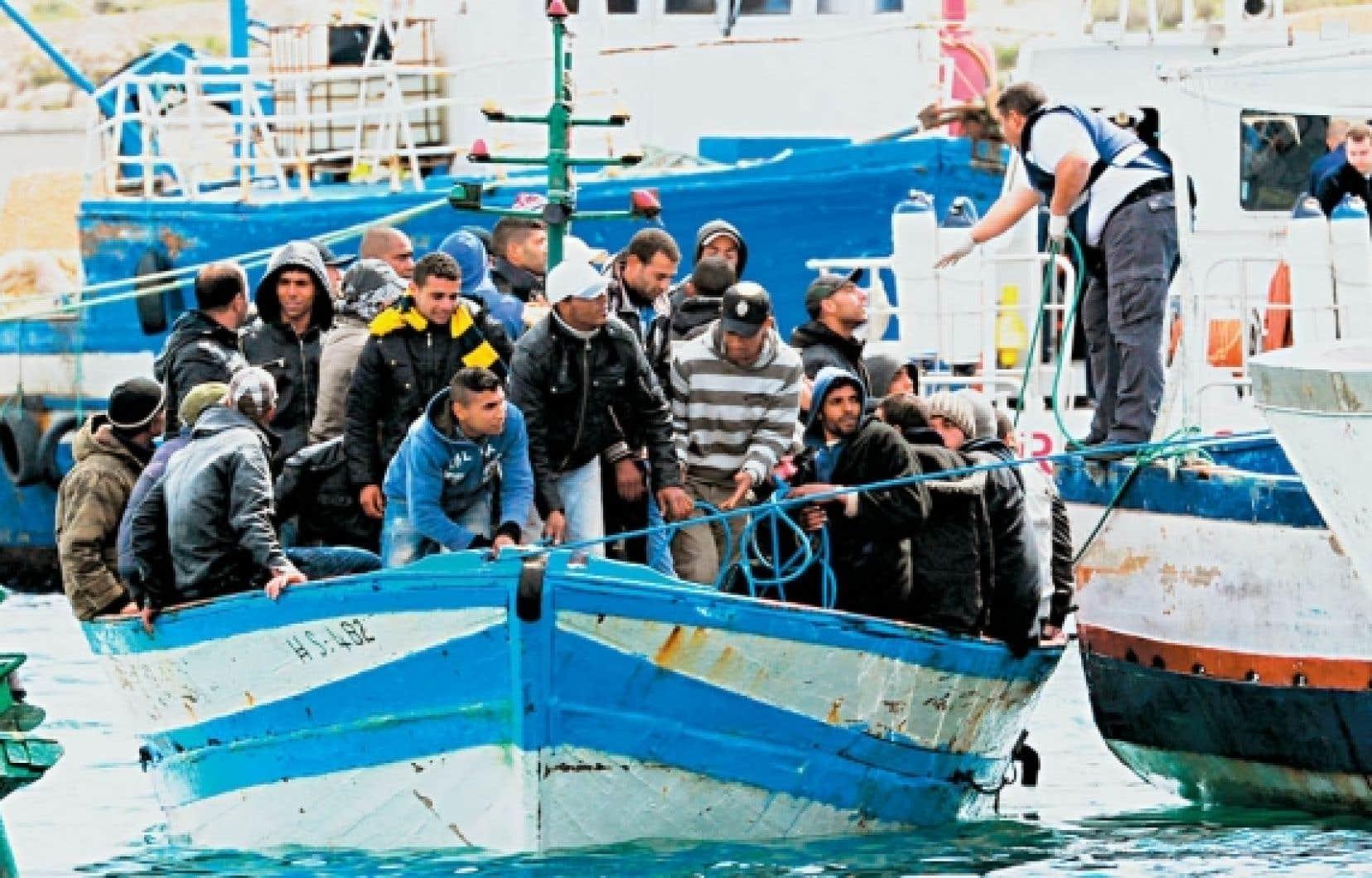 30 mars 2011: des immigrants tunisiens arrivent au port de Lampedusa, en Italie.<br />