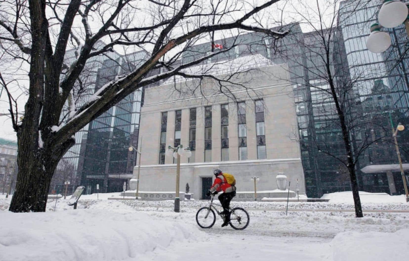 Un cycliste passe devant l'édifice de la Banque du Canada, à Ottawa. Selon les analystes, la banque centrale laisserait son taux directeur au niveau plancher pendant au moins un an.<br />