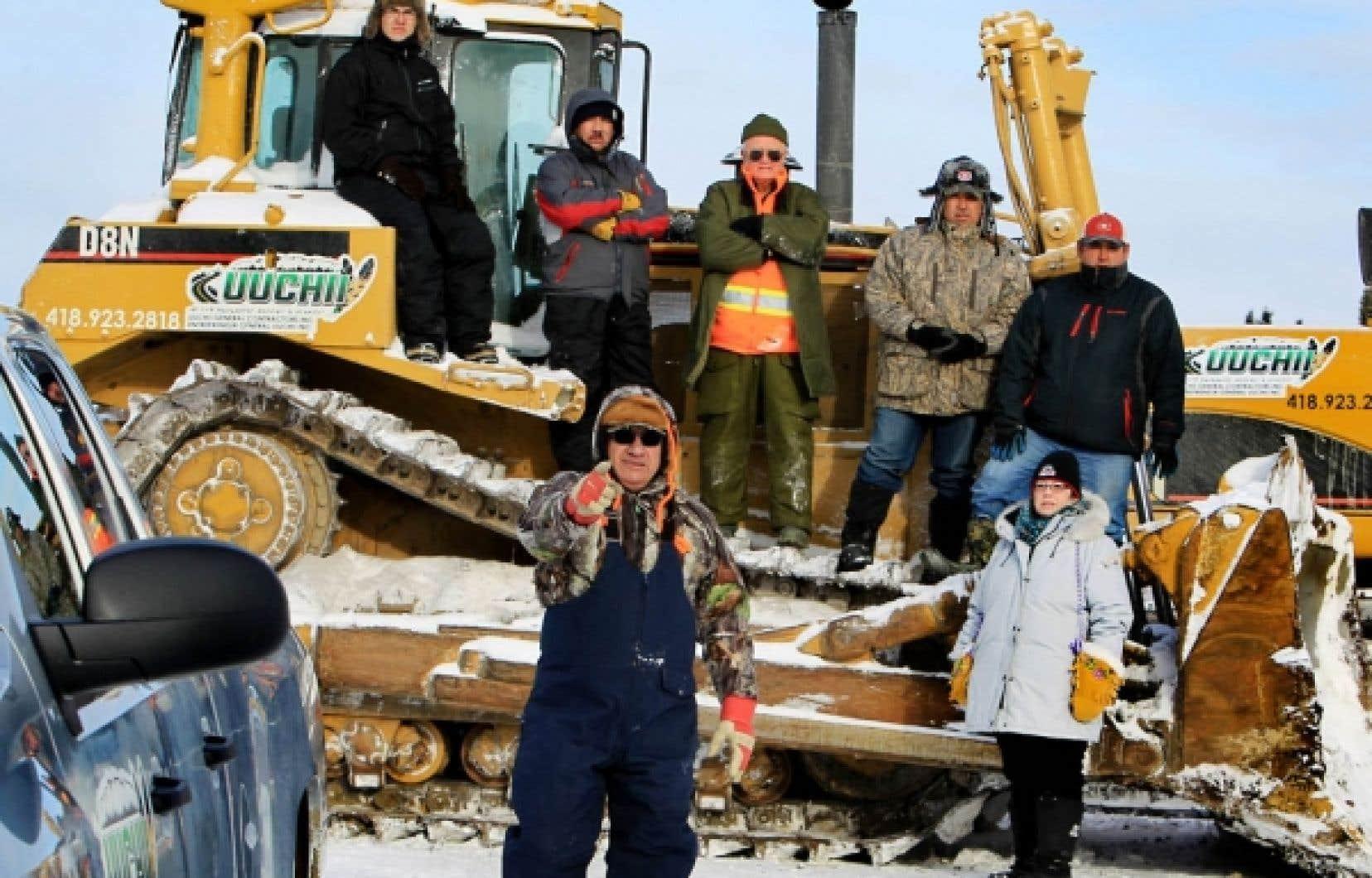 Christopher Matoush, Daniel Mattawashish, Jocelyn Deschamps, Simon Mattawashish, Roger Mattawashish, Emma Mattawashish et, à l'avant-scène, Coome Matoush, ont érigé une barricade pour dénoncer l'octroi du contrat du prolongement de cette route du nord québécois.